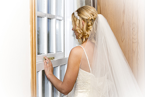 Bride looks at the window at swancar