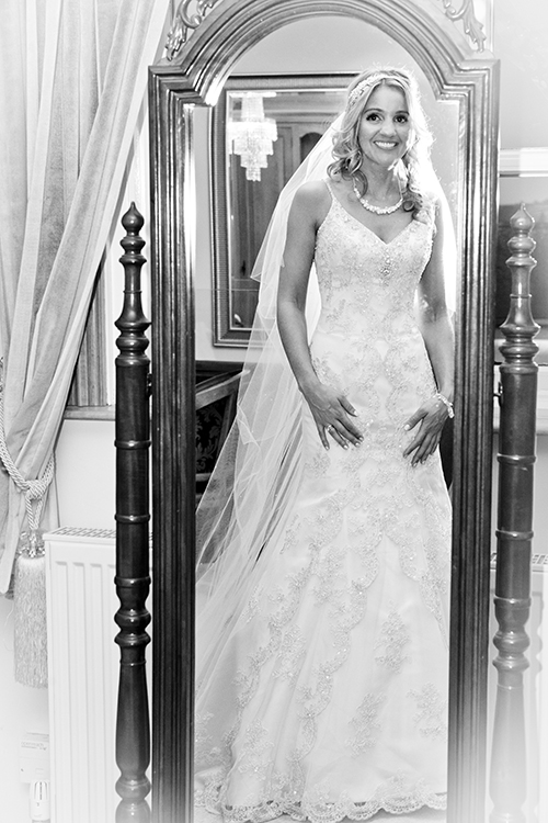 brides looks in mirror on day of wedding