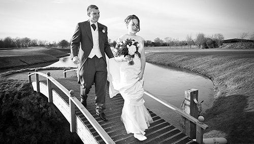 bride and groom walk over bridge