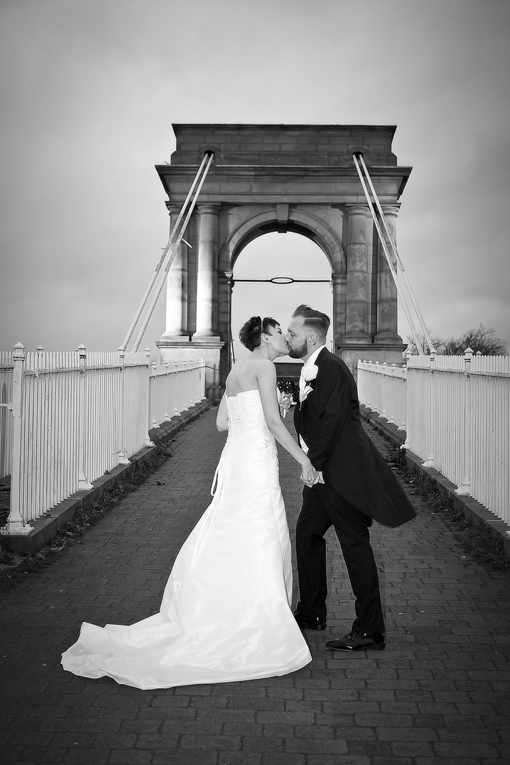 wedding couple kiss by bridge