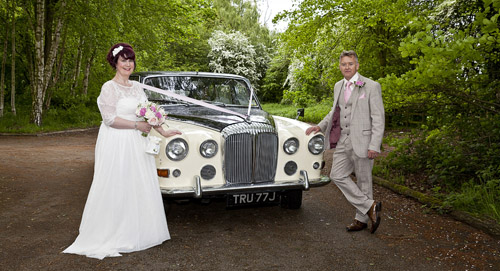 bride and groom stand by wedding car