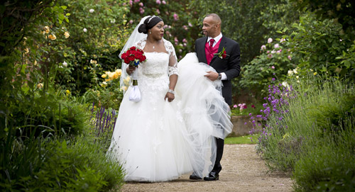 groom holds the brides dress